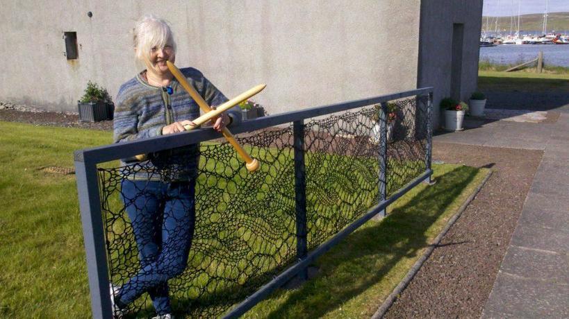 С гигантскими спицами в руках: женщина вяжет кружевные заборы