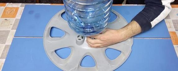 Из старого диска от автомобильного колеса и пластиковой бутылки сделала удобную поилку для курей